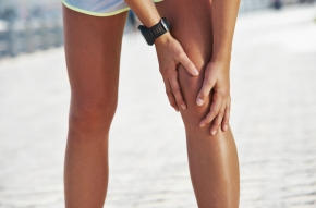 A young female runner holding onto her knee as if she is in pain
